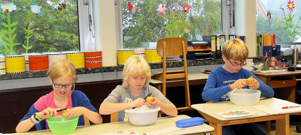 Kinder aus den 3. Klassen schälen Kartoffeln